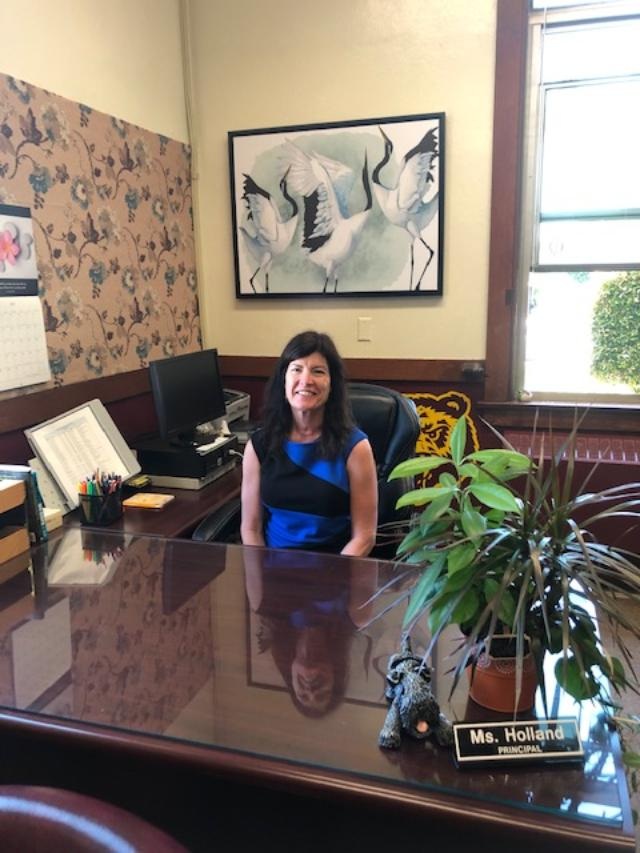 Principal Holland sits behind new desk.