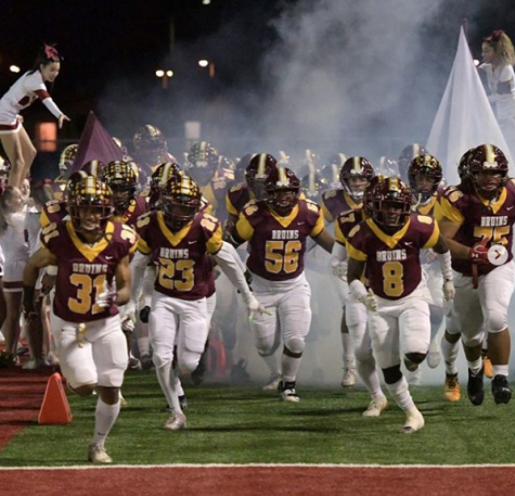 Seniors, Peter Sio (31), Jerimiah Artis (23), Jorge Jimenez (56), and Junior Tyrie Robinson (8) enter the field as they sprint down a line of fog, cheerleaders, bruinettes, and band members.